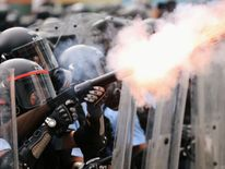 A police officer fires tear gas at protesters during a demonstration against a proposed extradition bill in Hong Kong