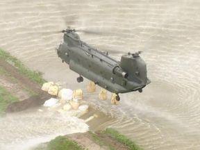 An RAF chinook drops sandbags in Wainfleet, Lincolnshire