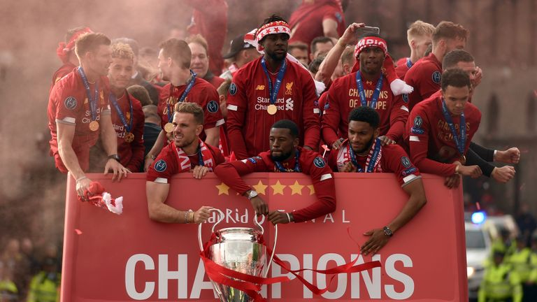 Liverpool's English midfielder Jordan Henderson and Liverpool's Dutch midfielder Georginio Wijnaldum hold the European Champion Clubs' Cup trophy, with teammates Liverpool's English midfielder James Milner, Liverpool's English midfielder Alex Oxlade-Chamberlain, Liverpool's Belgian striker Divock Origi, Liverpool's English striker Daniel Sturridge Liverpool's English defender Joe Gomez and Liverpool's English defender Trent Alexander-Arnold during an open-top bus parade around Liverpool, north-west England on June 2, 2019, after winning the UEFA Champions League final football match between Liverpool and Tottenham. - Liverpool's celebrations stretched long into the night after they became six-time European champions with goals from Mohamed Salah and Divock Origi to beat Tottenham -- and the party was set to move to England on Sunday where tens of thousands of fans awaited the team's return. The 2-0 win in the sweltering Metropolitano Stadium delivered a first trophy in seven years for Liverpool, and -- finally -- a first win in seven finals for coach Jurgen Klopp. (Photo by Oli SCARFF / AFP)        (Photo credit should read OLI SCARFF/AFP/Getty Images)