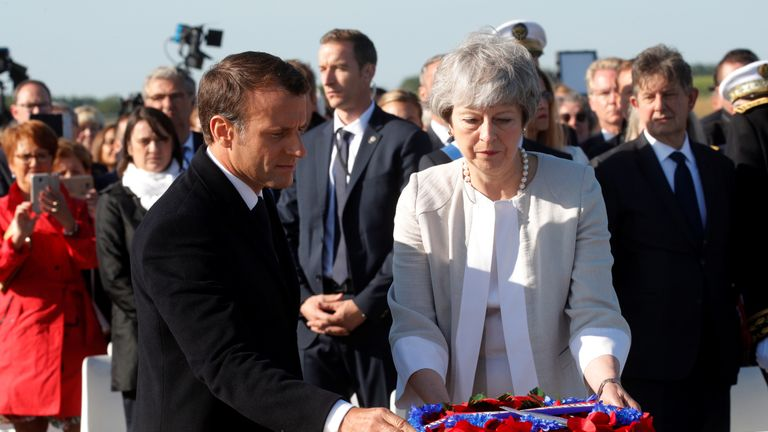 French President Emmanuel Macron and British Prime Minister Theresa May lay a wreath of flowers at the commemorative first stone of a British memorial.