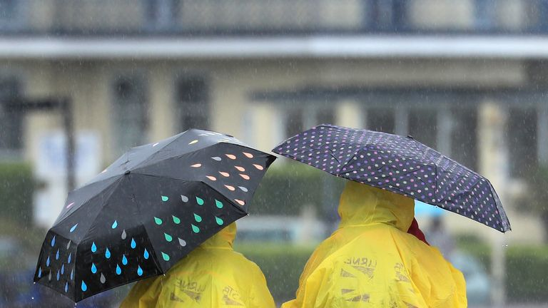 Two German exchange students brave torrential rain on the promenade in Eastbourne, Sussex.