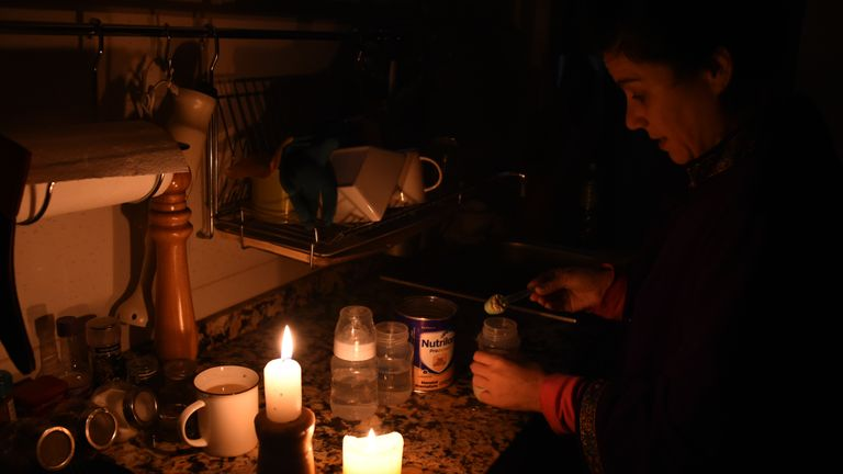 TOPSHOT - A woman prepares milk bottles using candles at her home in Montevideo on June 16, 2019 during a power cut. - A massive outage blacked out Argentina and Uruguay Sunday, leaving both South American countries without electricity, power companies said. (Photo by MIGUEL ROJO / AFP)        (Photo credit should read MIGUEL ROJO/AFP/Getty Images)