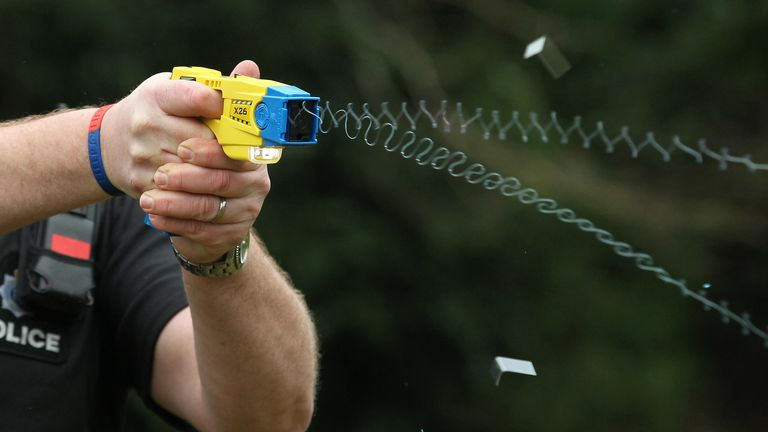 File photo 26/02/13 of a police officer demonstrating the use of a Taser as a majority of the public think it is acceptable for police to carry Tasers when on patrol, a survey suggests.