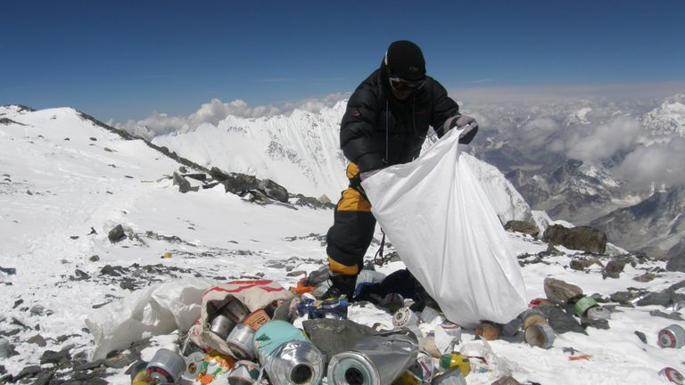 This picture taken on May 23, 2010 shows a Nepalese sherpa collecting garbage, left by climbers, at an altitude of 8,000 metres during the Everest clean-up expedition at Mount Everest. A group of 20 Nepalese climbers, including some top summiteers collected 1,800 kilograms of garbage in a high-risk expedition to clean up the world's highest peak. Led by seven-time summiteer Namgyal Sherpa, the team braved thin air and below freezing temperatures to clear around two tonnes of rubbish left behind by mountaineers, that included empty oxygen cylinders and corpses. Since 1953, there have been some 300 deaths on Everest. Many bodies have been brought down, but those above 8,000 metres have generally been left to the elements -- their bodies preserved by the freezing temperatures. The priority of the sherpas had been to clear rubbish just below the summit area, but coordinator Karki said large quantities of refuse was collected from 8,000 meters and below. AFP PHOTO/Namgyal SHERPA (Photo credit should read NAMGYAL SHERPA/AFP/Getty Images)