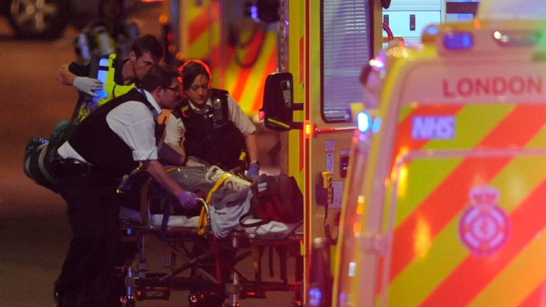 TOPSHOT - Police officers and members of the emergency services attend to a person injured in an apparent terror attack on London Bridge in central London on June 3, 2017. Armed police fired shots after reports of stabbings and a van hitting pedestrians on London Bridge on Saturday in an incident reminiscent of a terror attack in March just days ahead of a general election. / AFP PHOTO / DANIEL SORABJI        (Photo credit should read DANIEL SORABJI/AFP/Getty Images)