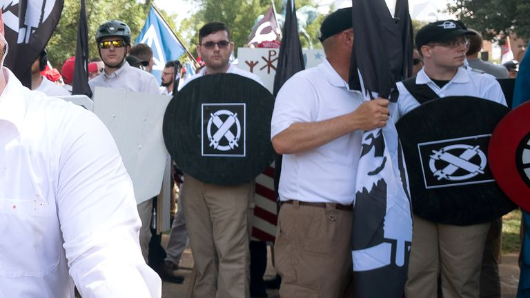 "James Alex Fields Jr., (2nd L with shield) is seen attending the ""Unite the Right"" rally in Emancipation Park before being arrested by police and charged with charged with one count of second degree murder, three counts of malicious wounding and one count of failing to stop at an accident that resulted in a death after police say he drove a car into a crowd of counter-protesters later in the afternoon in Charlottesville, Virginia, U.S., August 12, 2017. Picture taken August 12, 2017  REUTERS/Eze Amos"