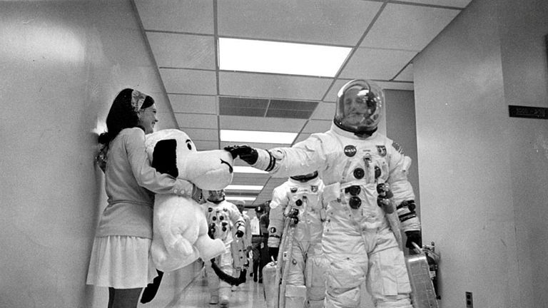 Mission commander Thomas P. Stafford pats the nose of Snoopy, the mission's mascot, as the Apollo 10 crew walks along a corridor