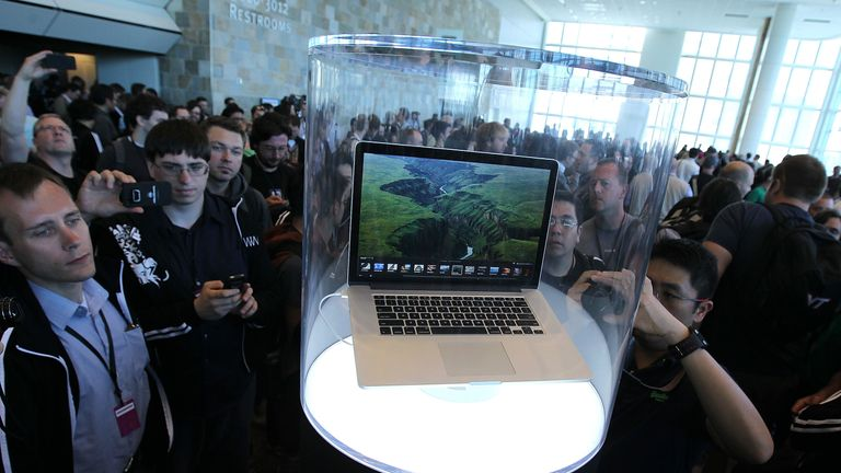 People gather around a MacBook Pro that is displayed at the 2012 Apple WWDC keynote address
