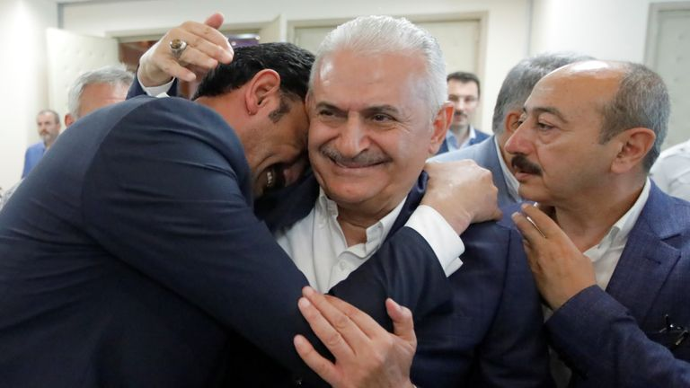 Binali Yildirim is hugged by a supporter of Turkey's ruling party