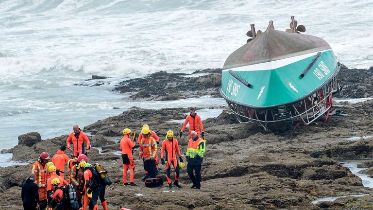 Rescuers work near the capsized boat