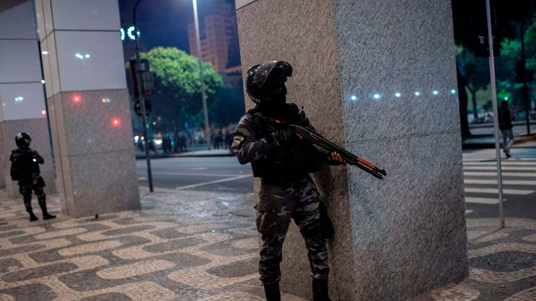 A Brazilian riot Police officer hides after shooting rubber bullets against demostrators
