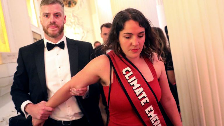 "LONDON, ENGLAND - JUNE 20: Climate change protester is escorted out after interrupting British Chancellor of the Exchequer Philip Hammond's speech during the annual Mansion House dinner on June 20, 2019, in London, England. Greenpeace volunteers wearing red evening dress with sashes reading ""climate emergency"" gatecrashed and disrupted the beginning of Chancellor Philip Hammond's Mansion House speech. (Simon Dawson - WPA Pool/Getty Images)"