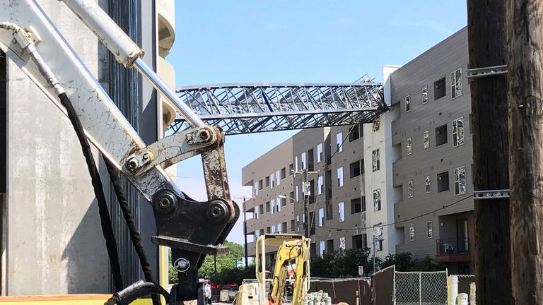 This photo provided by Scott Flodin shows a crane that fell on an apartment building amid severe thunderstorms