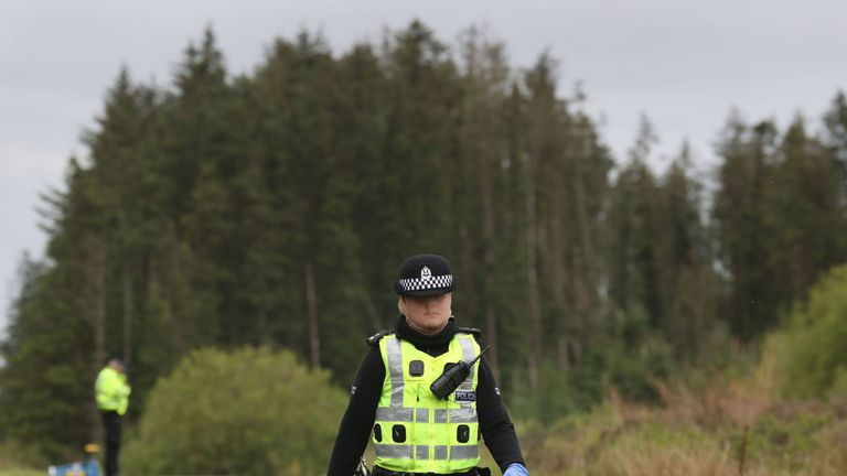 Police officers protect themselves from midges in Galloway Forest in Dumfries and Galloway