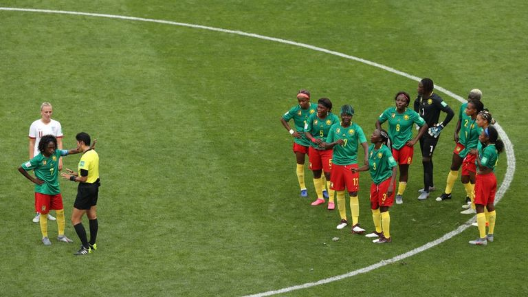 A Cameroon player complains to the referee after England's second goal