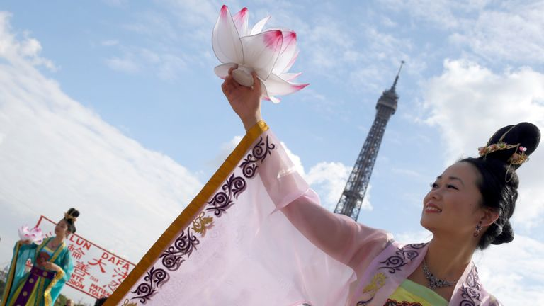 Falun Gong members perform in front of the Eiffel Tower in Paris in a protest against organ harvesting