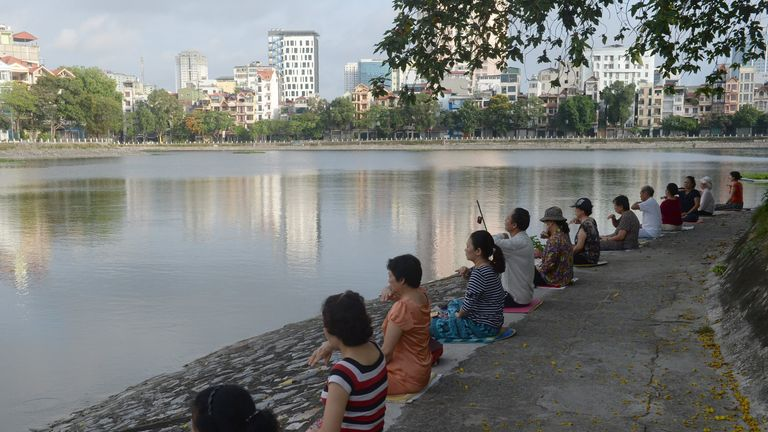 This picture taken on June 10, 2017 shows residents practicing Falun Gong meditation exercises next to a lake in downtown Hanoi