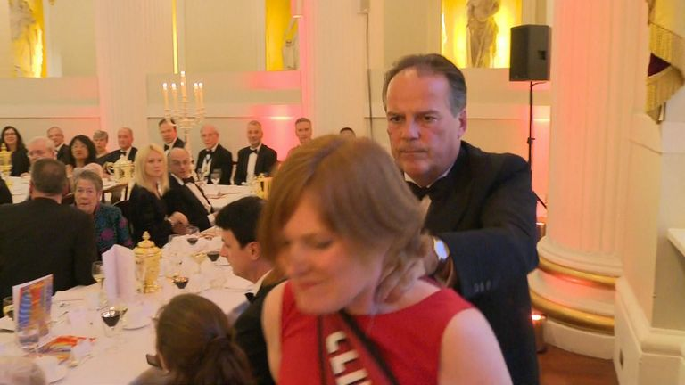 MP Mark Field pushes a climate change protester out of an event at Mansion House in London