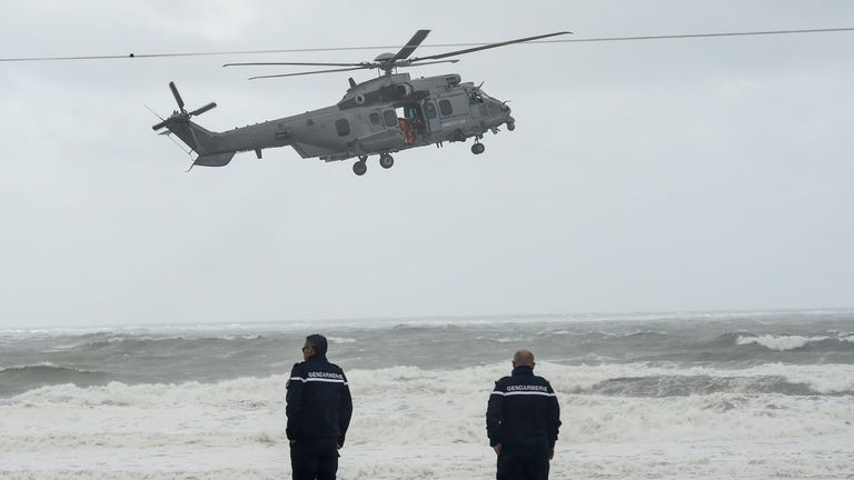 Two gendarmes look on as a French Air Force helicopter flies over a beach in Les Sables-d'Olonne
