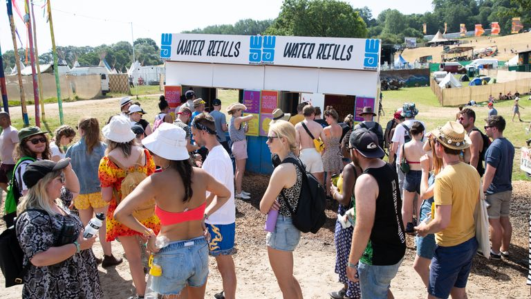 Festival goers queue for water at a refill station at the Glastonbury Festival