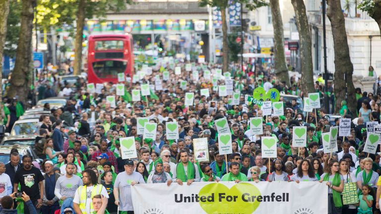 People take part in a silent walk by Grenfell Tower, to mark one year since the blaze which claimed 72 lives in 2018