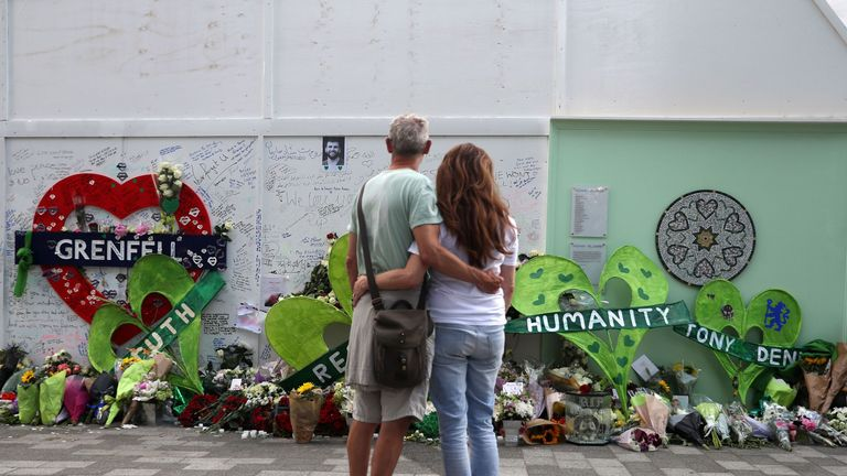 A couple observe the memorial at the base of Grenfell Tower