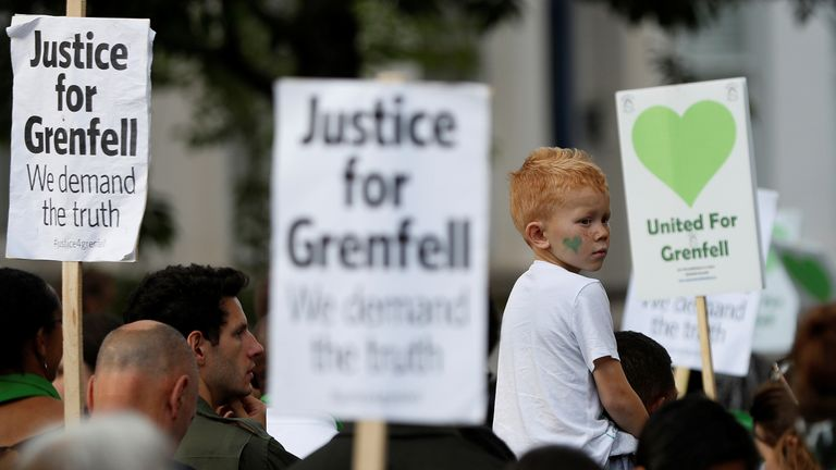 A child sits on his father's shoulders during a Silent March marking the first anniversary of the Grenfell Tower fire