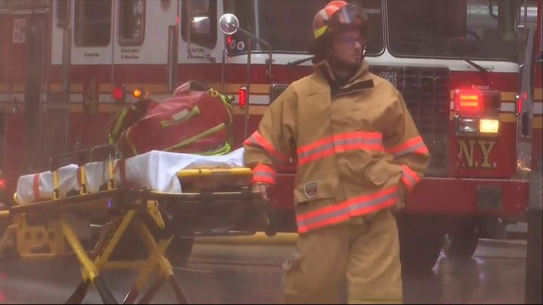 A firefighter carries a stretcher at the scene of the incident
