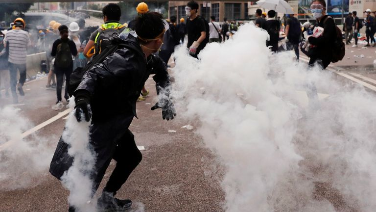 A protester throws a tear gas canister during demonstrations in Hong Kong