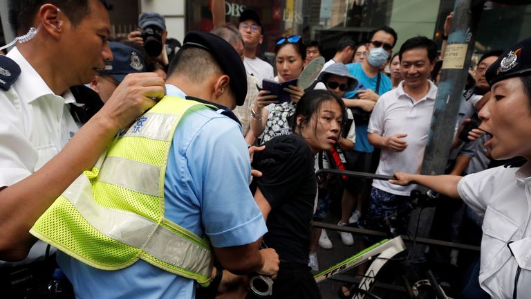Police officers detain a demonstrator during a protest to demand authorities scrap a proposed extradition bill with China
