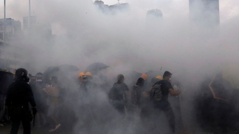 Protesters react to a tear gas during a demonstration against a proposed extradition bill in Hong Kong