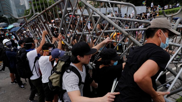Protesters try to tear down police barricades
