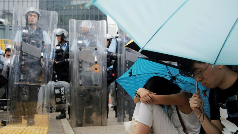 rotesters holding umbrellas occupy a street near a row of police officers outside the Legislative Council building during a demonstration against a proposed extradition bill in Hong Kong, China June 12, 2019.