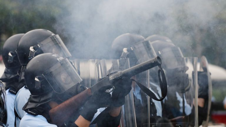 Police officer fires tear gas at protesters during a demonstration against a proposed extradition bill in Hong Kong