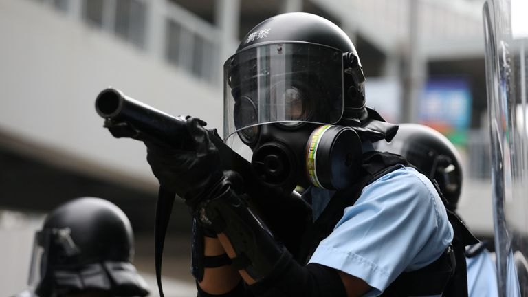 Police officer aims a tear gas gun at protesters during a demonstration against a proposed extradition bill in Hong Kong