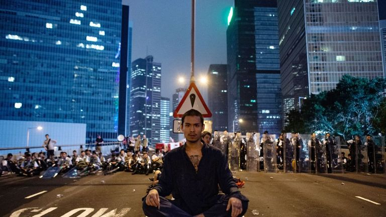 TOPSHOT - A protester (C) sits at the middle of Harcourt Road in Hong Kong after a protest against a controversial extradition law proposal in Hong Kong on June 12, 2019. - Violent clashes broke out in Hong Kong on June 12 as police tried to stop protesters storming the city's parliament, while tens of thousands of people blocked key arteries in a show of strength against government plans to allow extraditions to China. (Photo by Philip FONG / AFP) (Photo credit should read PHILIP FONG/AFP/Getty