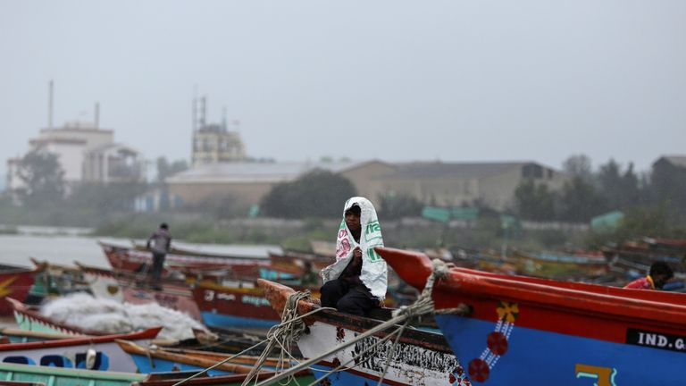 A boy covers himself from rain as he sits on a fishing boat along the shore ahead of Cyclone Vayu in Veraval