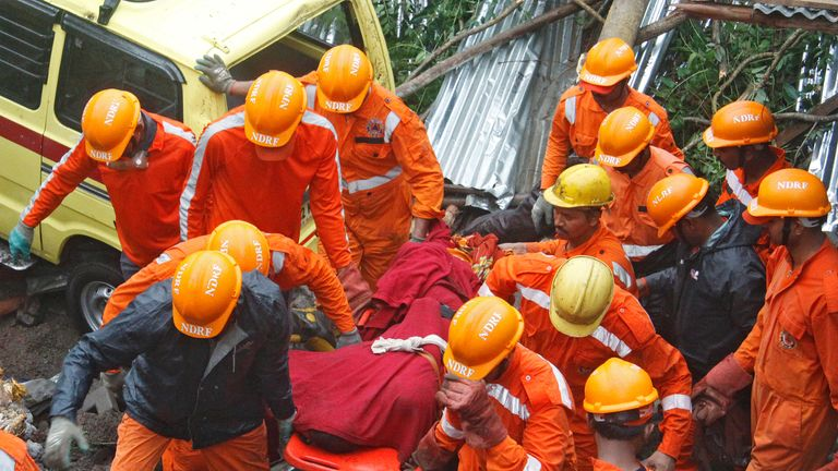 Rescue workers carry the body of a victim at the site of a collapsed wall