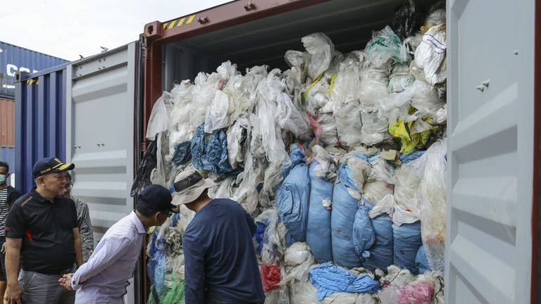 Indonesian customs officers examine one of 65 containers full of imported plastic rubbish, at the Batu Ampar port in Batam