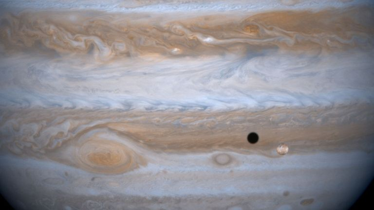 383787 01: The entire body of Moon-sized Io, as it casts a black shadow, is captured here alongside the planet Jupiter in this picture taken by NASA's Cassini spacecraft, December 3, 2000. Jupiter's other moon, Ganymede is larger than the planets Mercury and Pluto and Saturn's largest moon, Titan. Both Ganymede and Titan have greater surface area than the entire Eurasian continent on our planet. Cassini was 26.5 million kilometers (16.5 million miles) from Ganymede when this image was taken. The