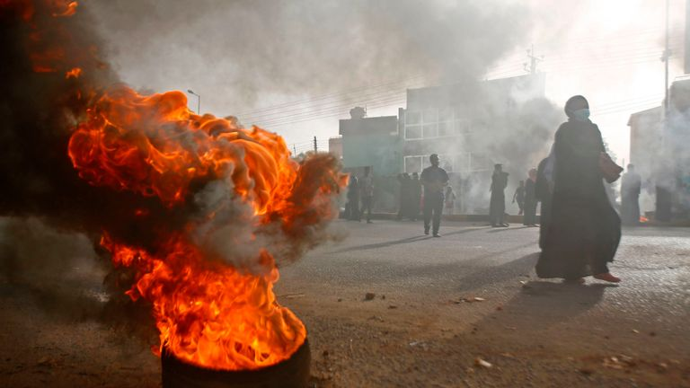 A tire burns outside army HQ in Khartoum