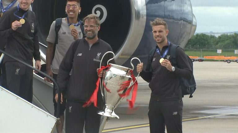 Liverpool team arrive in the UK with the Champions League trophy.