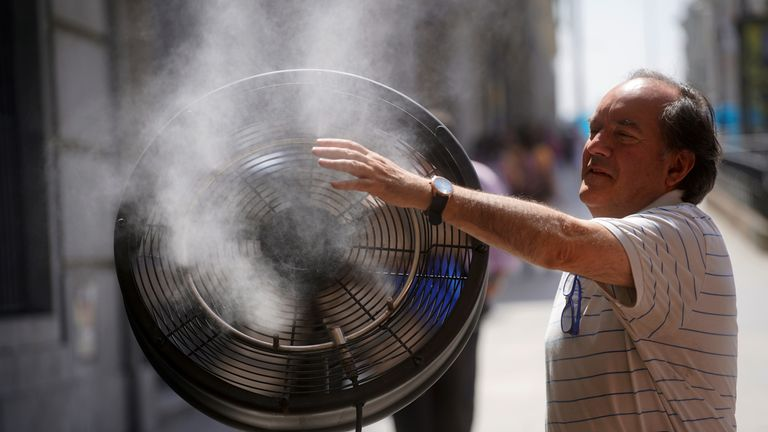 A man tries to cool himself with a fan in central Madrid, Spain, June 27, 2019