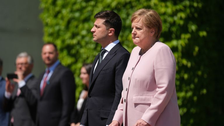 Merkel listens to the German national anthem as she stands on a hot day with new Ukrainian President Volodymyr Zelensky