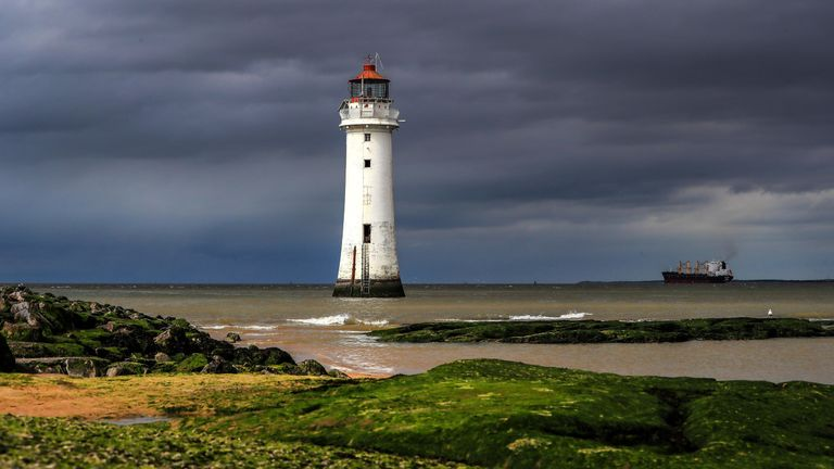 A container ship sails out of the River Mersey past New Brighton lighthouse