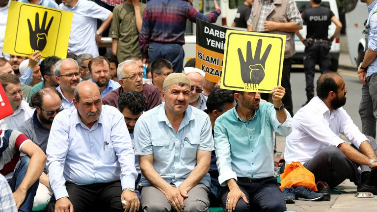 """People holds placard depicting the symbol """"Rabaa"""" of the supporters of  Mohamed Morsi in Ankara"""