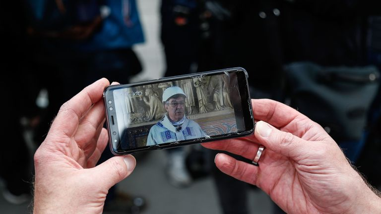 A person holds a mobile phone to watch a live feed of the first mass being led by the Archbishop of Paris Michel Aupetit, wearing a hard hat, inside a side chapel of the Notre-Dames de Paris Cathedral following the destructive April 15 fire, in Paris on June 15, 2019. - The Notre-Dame cathedral in Paris will host its first mass on June 15, 2019, exactly two months after the devastating blaze that shocked France and the world. For safety reasons, the mass led by Archbishop of Paris Michel Aupetit