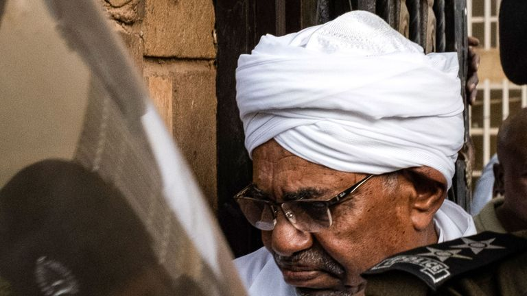 Sudan's ousted president Omar al-Bashir is escorted into a vehicle as he returns to prison following his appearance before prosecutors over charges of corruption and illegal possession of foreign currency, in the capital Khartoum on June 16, 2019