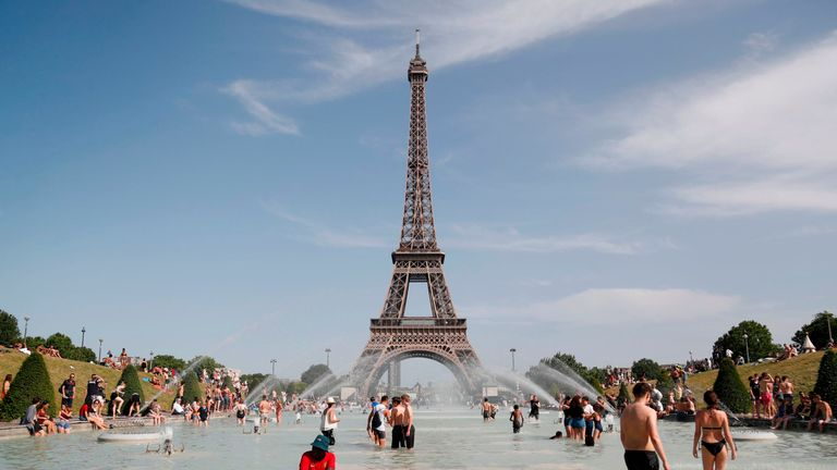 People try to keep cool in the Trocadero Fountain in front of the Eiffel Tower in Paris