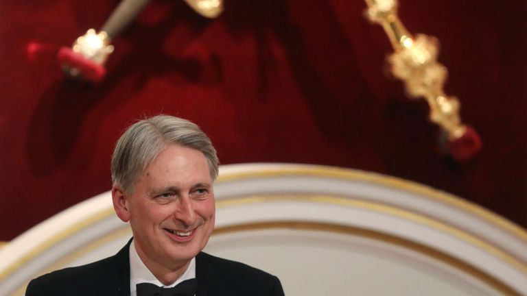 "LONDON, ENGLAND - JUNE 20: British Chancellor of the Exchequer Philip Hammond delivers a speech during the annual Mansion House dinner on June 20, 2019, in London, England. Greenpeace volunteers wearing red evening dress with sashes reading ""climate emergency"" gatecrashed and disrupted the beginning of Chancellor Philip Hammond's Mansion House speech. (Simon Dawson - WPA Pool/Getty Images)"